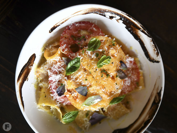 Pappardelle pasta with local organic tomato purée, olive oil, raw thinly sliced tomato, Parmigiano Reggiano, basil, black pepper and black garlic. Photo by  Anna Petrow .