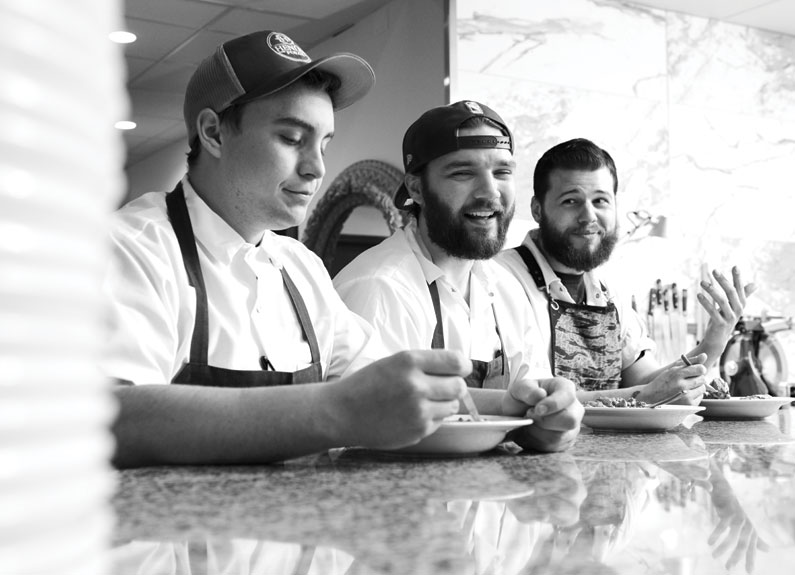 """From left, Louie cooks Alex Herman, Chris Krzysik and Mike """"noodles"""" McManus enjoy a family meal before service. // photo by    Greg Rannells"""
