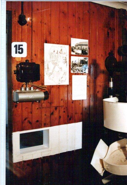 Hullet i veggen som brettene med ferdig fylte bokser ble sendt inn gjennom, til han som satte lokk på boksene med falsemaskinen. Maskinen bråkte så mye, at på denne måten slapp man å åpne døra til maskinrommet med falsemaskinen.