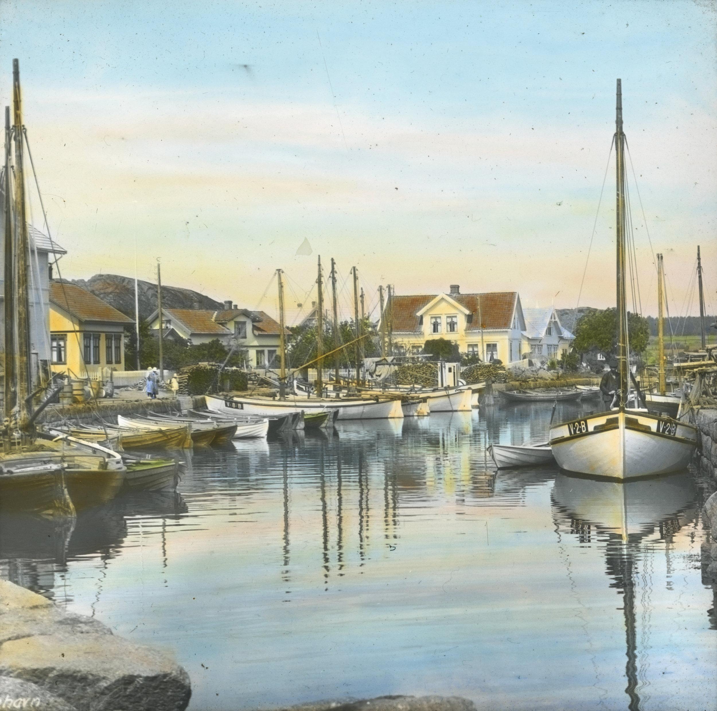 Håndkolorert dias. Seilbåter og robåter ligger fortøyd til kai i Nevlunghavn. I bakgrunnen sees hvitmalte trehus.  Fotograf: Wilse, Anders Beer / Norsk Teknisk Museum