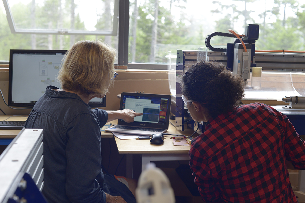 Two people discussing a design on a computer in the Haystack Fab Lab