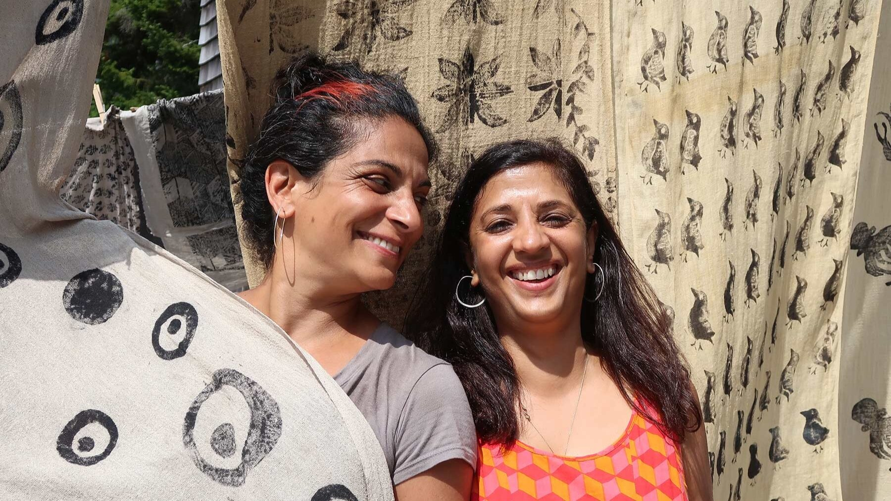 Two women smile in front of blockprinted textiles