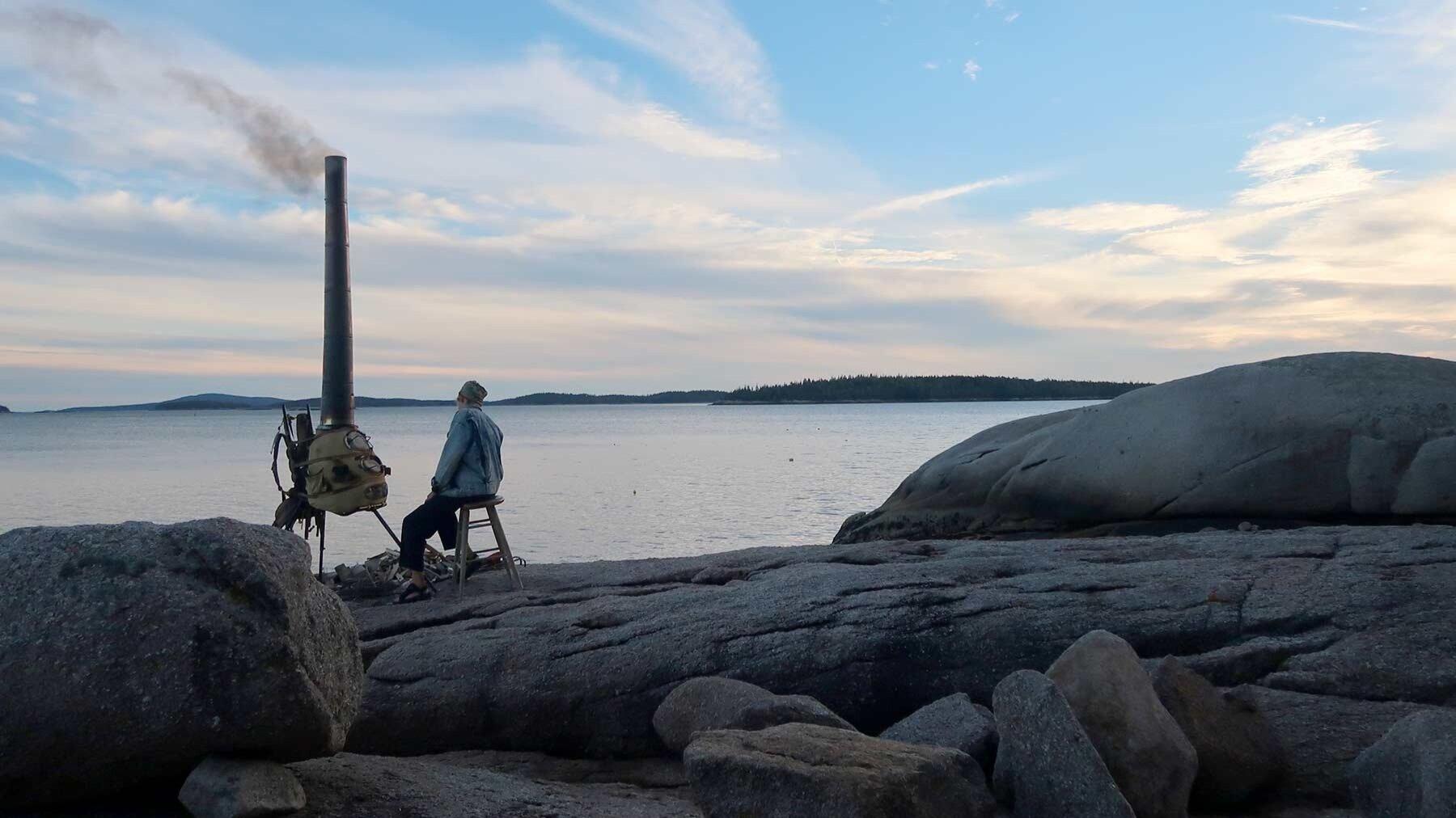 A man sits next to a handmade kiln near the ocean