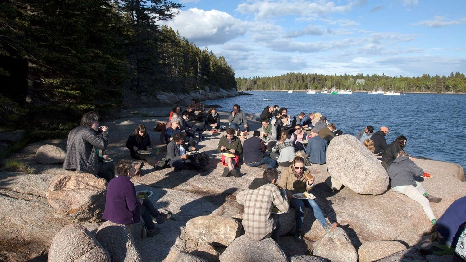 People sit on rocks near the ocean, eating lunch