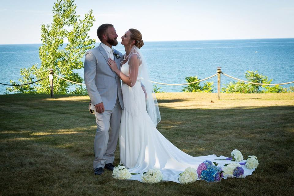 """Jillian 7/7/18 Photographer: Gene Avallone, owner of    Park Avenue Photo    """"Hello! I wanted to share a picture from our wedding. Me and my husband, Chris were married on July 7th of this year in Sodus Point, NY. I purchased my gorgeous Miss Stella York dress from you! I came to your store for that dress specifically. When I tried it on, I knew it was the one. I felt like a goddess in that dress on my wedding day. Janice and the entire Heart to Heart staff are the absolute best! The bridesmaids dresses were also purchased from your store. They were so stunning! Thank so much for helping make our day a true fairy tale."""""""