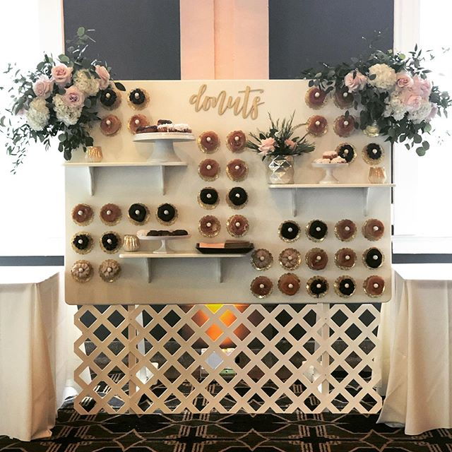 Donut Walls are all the rage and they are so much better with pretty blooms and a custom design thanks to the bride's stepdad! These treats went over so well that we only had 4 left at the end of the night. That RARELY happens! #nationaldonutday🍩