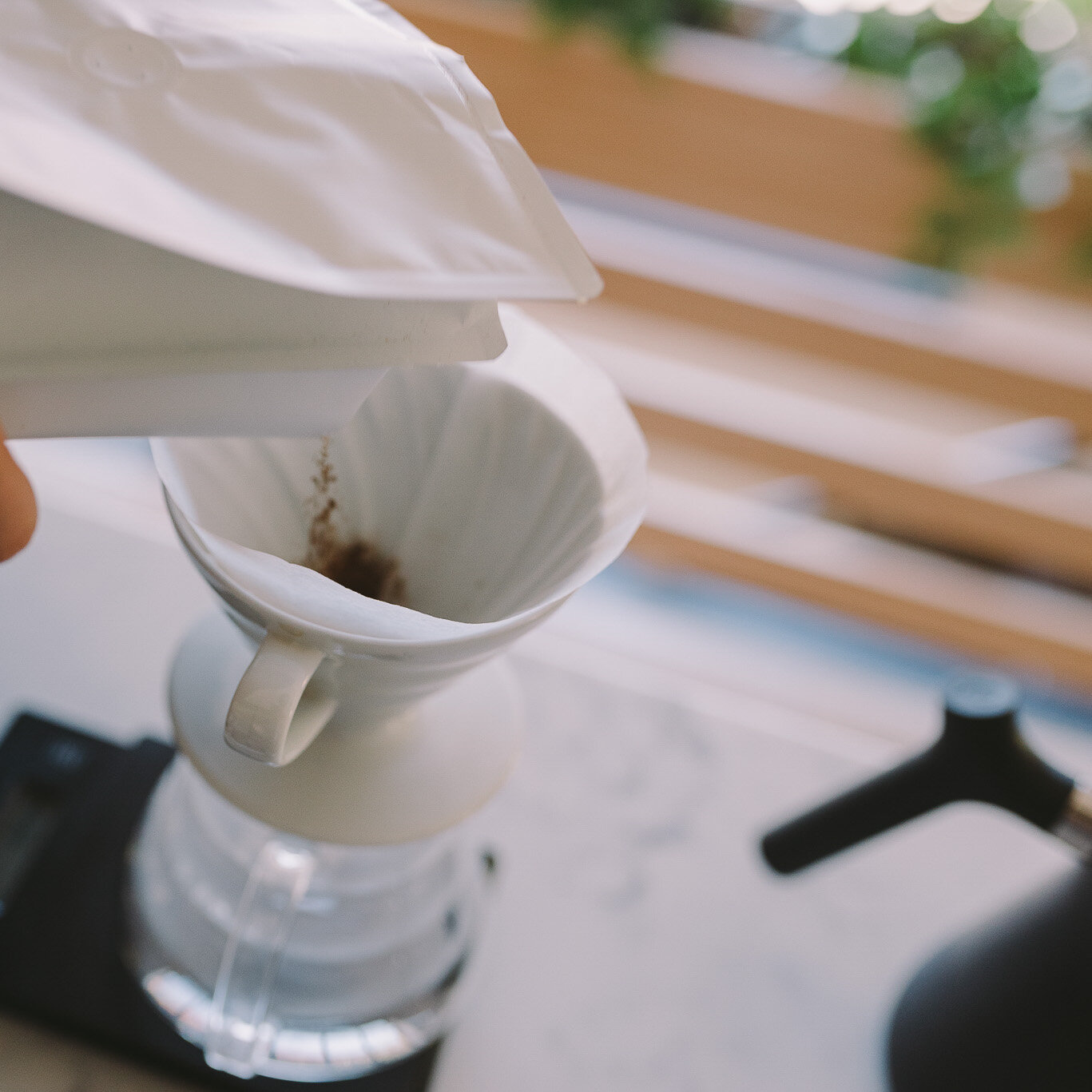 Adding coffee to V60 2 cup.
