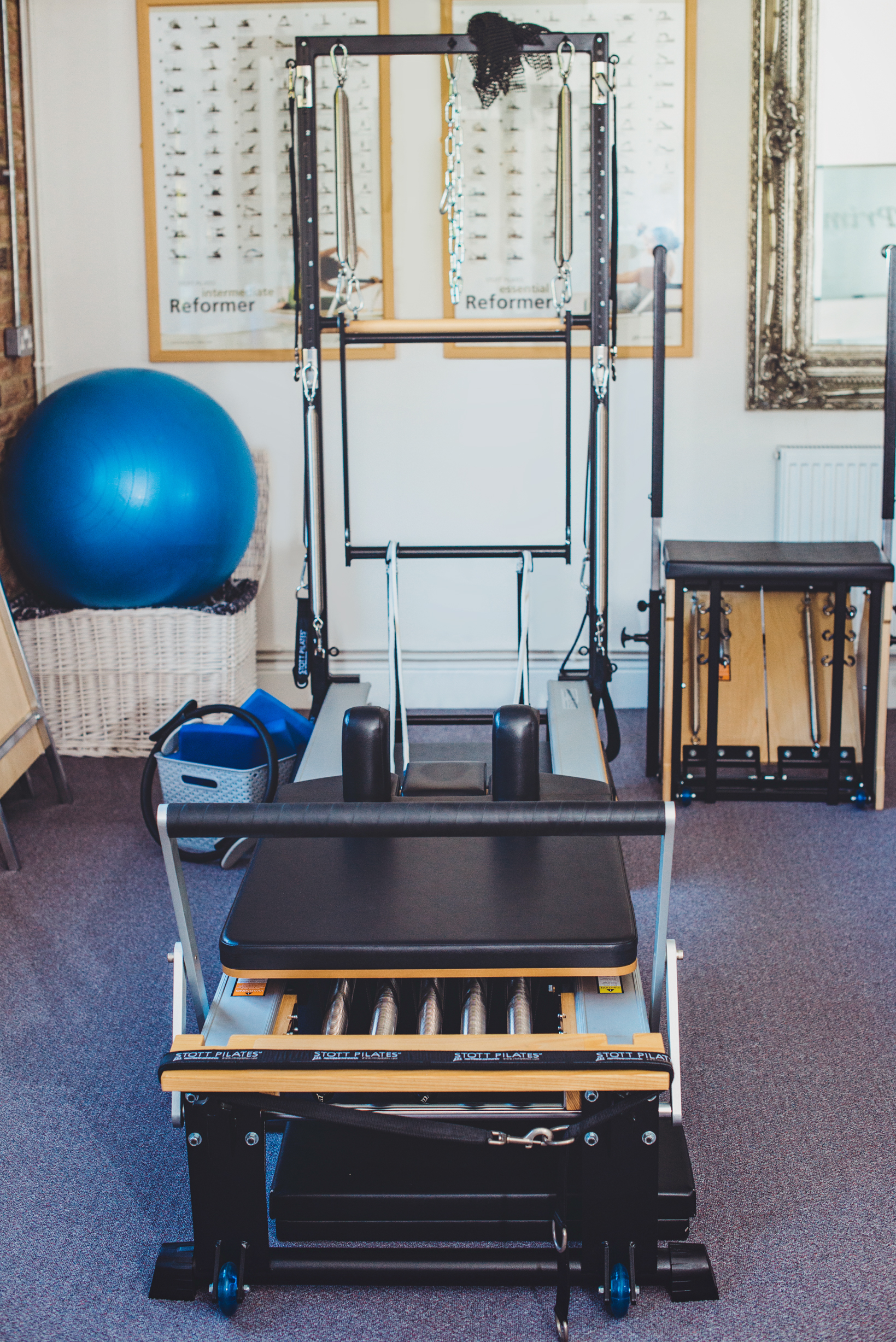 Reformer - The Reformer is the premier piece of Pilates equipment. It is a half bed like frame with a carriage on it, which rolls forward and backwards on wheels within the frame. The carriage is attached to one end of the reformer by springs which can be adjusted to different levels of resistance. There are shoulder rests at one end which stop you from sliding off as you move.The Reformer is very versatile. Exercises can be done laying down, sitting, standing, pulling the straps, pushing against the footbar, with additional equipment, upside-down, sideways and the list goes on.Exercises done on the Reformer increase core and functional strength, increase muscular endurance, improve posture and alignment, develop long lean muscles, reduce body fat, rehabilitate and prevent injuries.