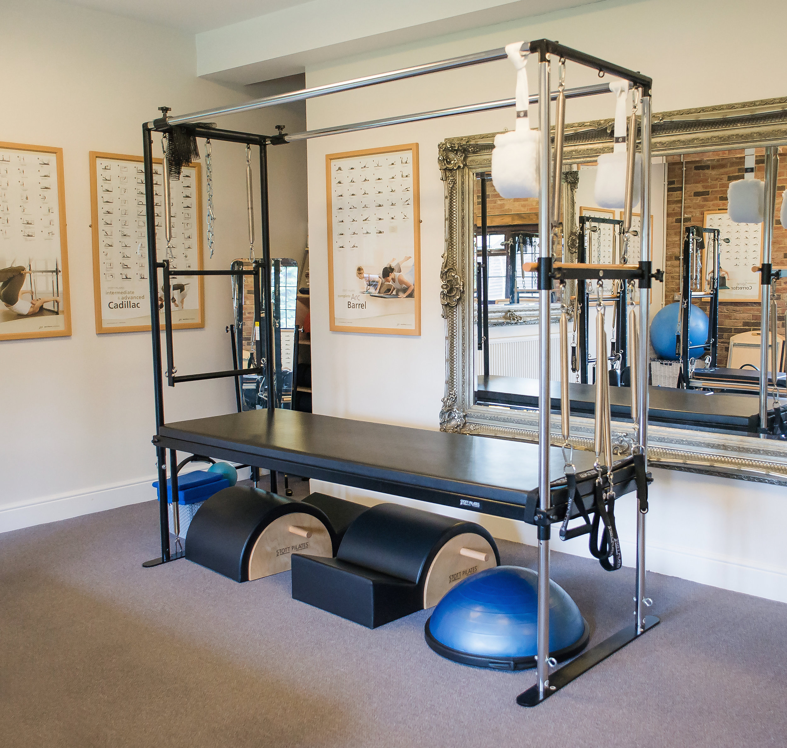 """Cadillac - No full service Pilates studio is complete without a Cadillac/Trapeze Table. It closely represents a bed with a frame, featuring a Roll-Down Bar, Push-Thru Bar, Trapeze, Leg and Arm Springs which are used to support and challenge. Joseph Pilates made all his creations in the basement of his building. When he brought it up into the studio, one of his clients saw the table and said """"Hey Joe, is that your new Cadillac?"""" and the name stuck. The Cadillac offers a extensive range of exercises for everyone from post-rehab clients to athletes, challenging the body in different plans of motion."""