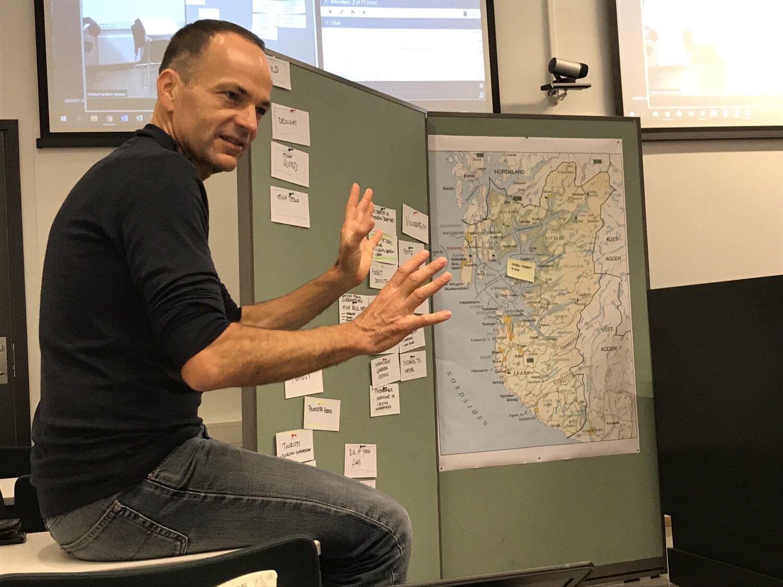 Marc Zebisch frå Eurac Resarch framfor tavla der analysen av klimarisikoen skogbrann er i ferd med å få kjøt på beinet. Til høgre: kartet over Rogaland. Den gule lappen viser plasseringa av øya Ombo, som deltakarane på arbeidsverkstaden tok for seg.
