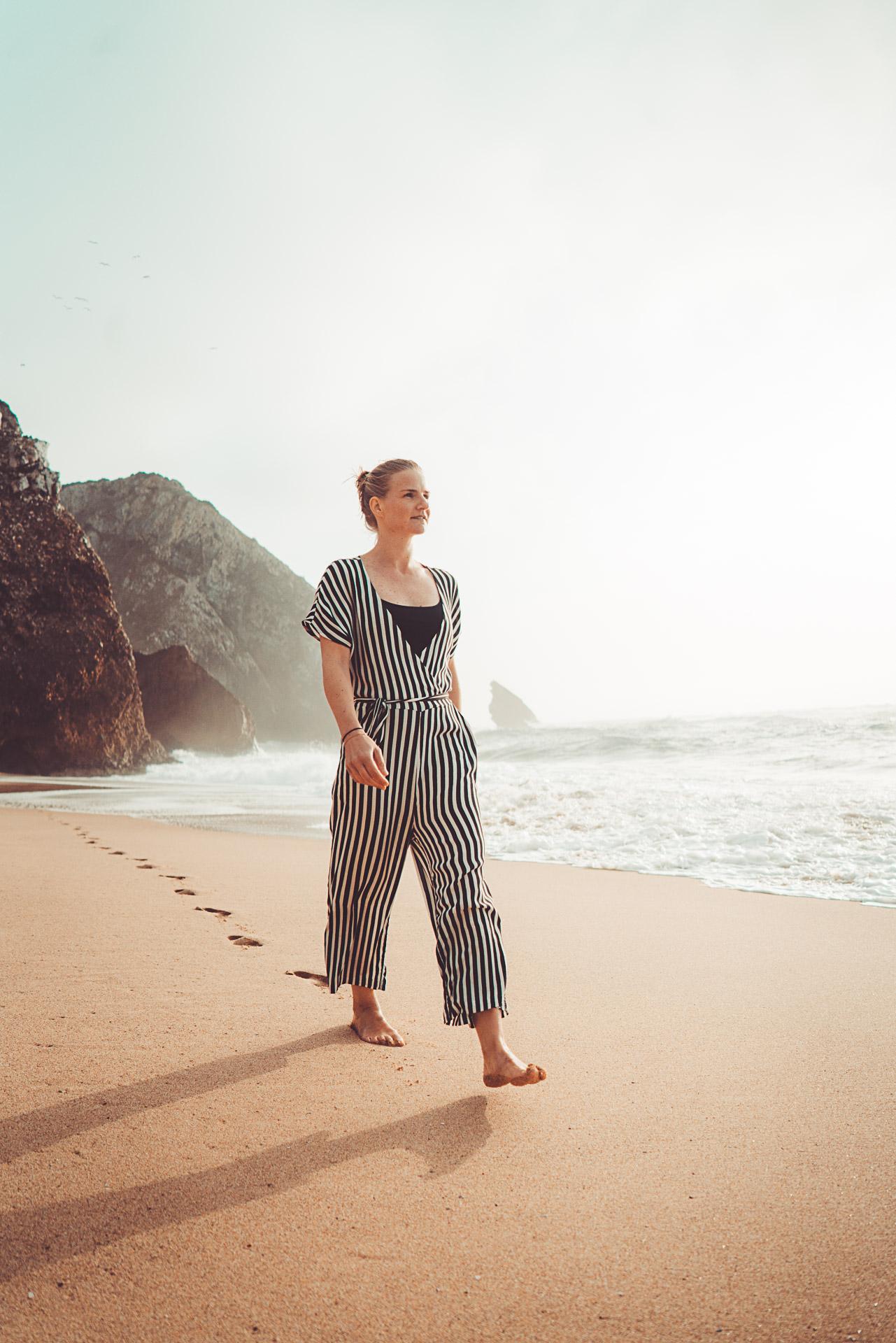 Woman walking along a beach_Courage Adventures