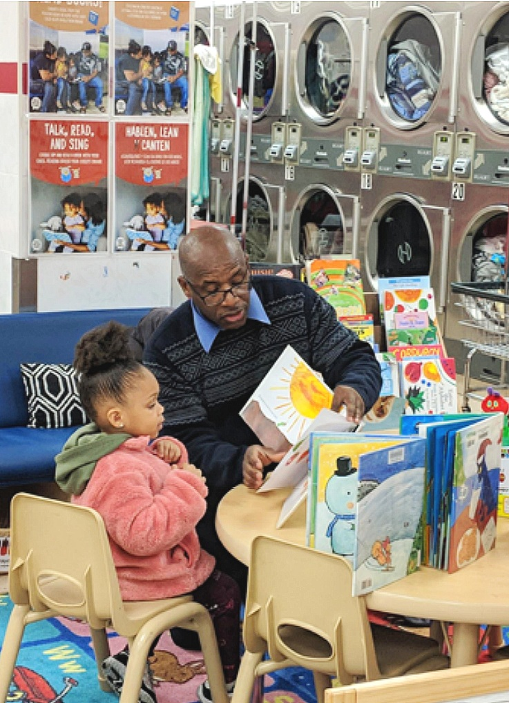 "Librarian engaging with a child at a ""Laundry & Literacy Kit"" launch site in New York."