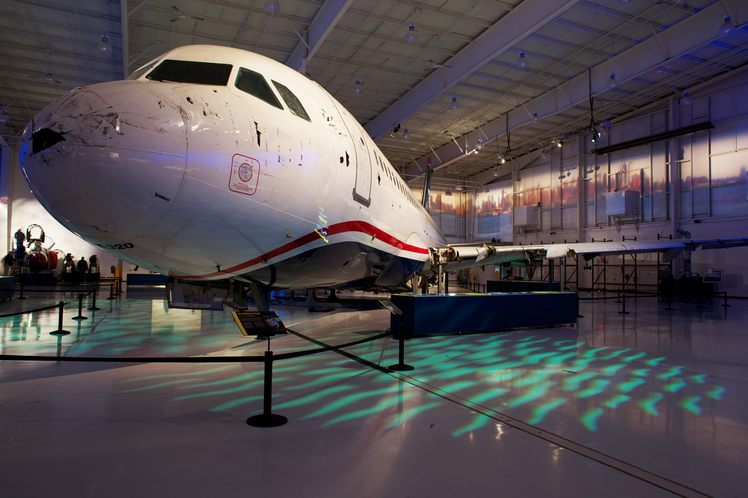Carolinas Aviation Museum, North Carolina, USA. High-end multimedia technologies of theatrical lighting and audio-visual displays are used to activate the aircraft, and spatial planning is carefully managed to ensure seamless flow of visitors between enormous artefacts.