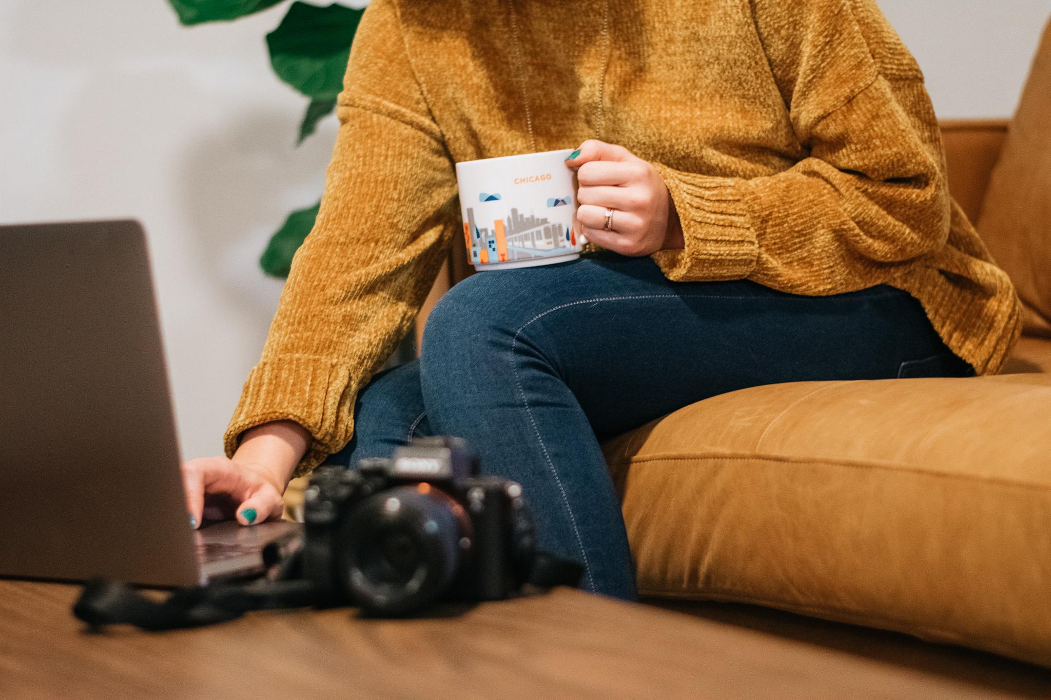 woman using computer holding mug