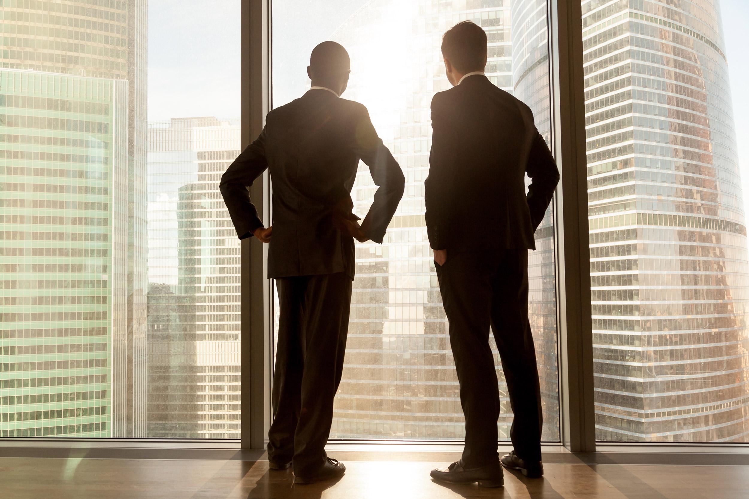 Two Australian men looking outside the building