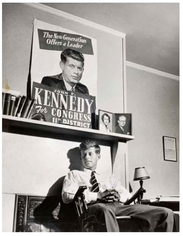 John F. Kennedy, age 29, sitting under a campaign poster in a room at the Bellevue Hotel during his 1946 campaign. On the mantle are photos of his parents. Photograph by Joel Yale for Life magazine.