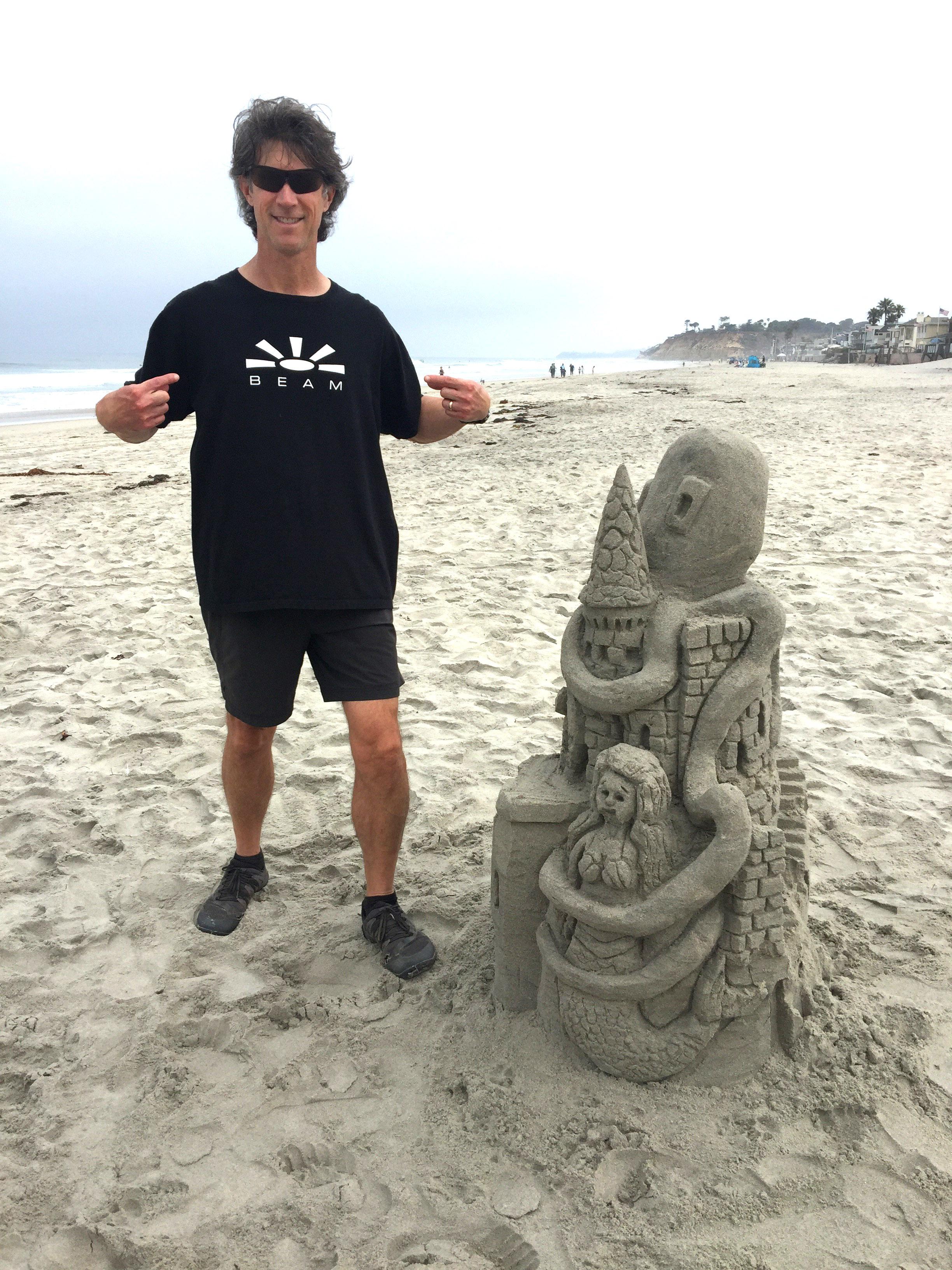 Rich Trissel - CaliforniaRich 'BEAMs' next to his impressive sand creation on the beach in Del Mar, California.