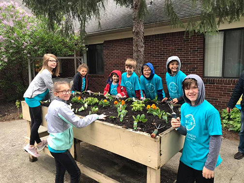 Lower school students planting flowers and vegetables at Carmel Health and Living.