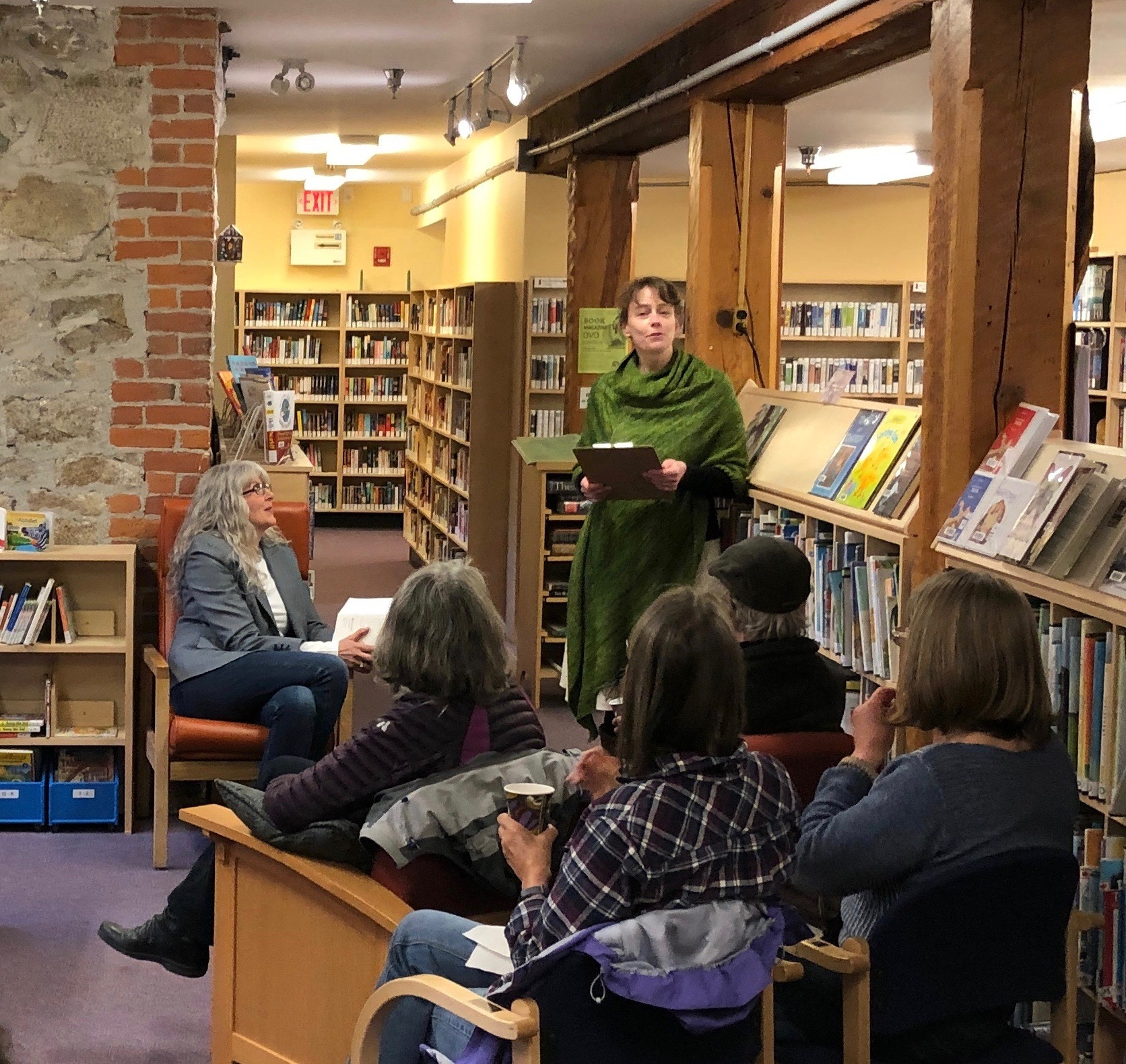 """Kaslo Librarian, Angela Bennett, spent a few moments introducing me and sharing her impressions of my memoir. The library, in its current incarnation, is housed in the town space that operated as the jail from 1898-1913 and then became a storage space for public works. It had a dirt floor when renovations began in 1979! The Local History room, behind me with the partial red brick wall, was renovated in 2008 as part of a BC150 celebration project to open the 1898 """"dark cell"""" which was used for solitary confinement of prisoners. If you're ever in Kaslo, which is a fascinating, gorgeous town north of Nelson in the West Kootenays, you have to come check it out!"""