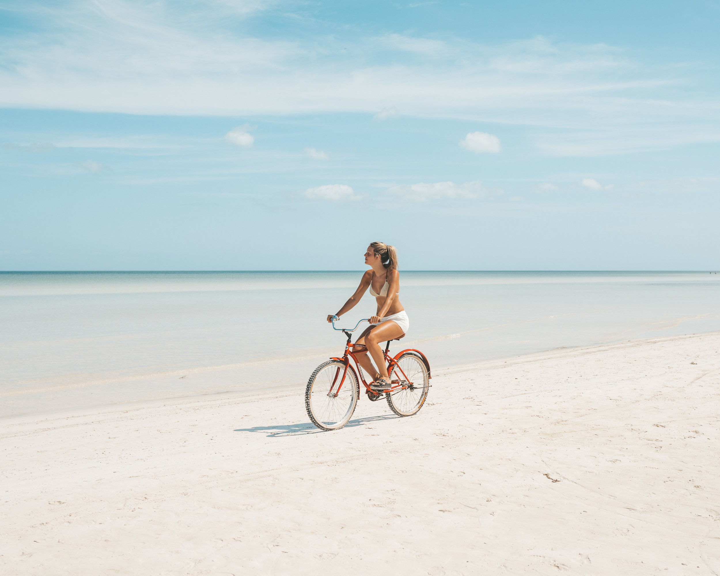 girl-cycling-on-beach
