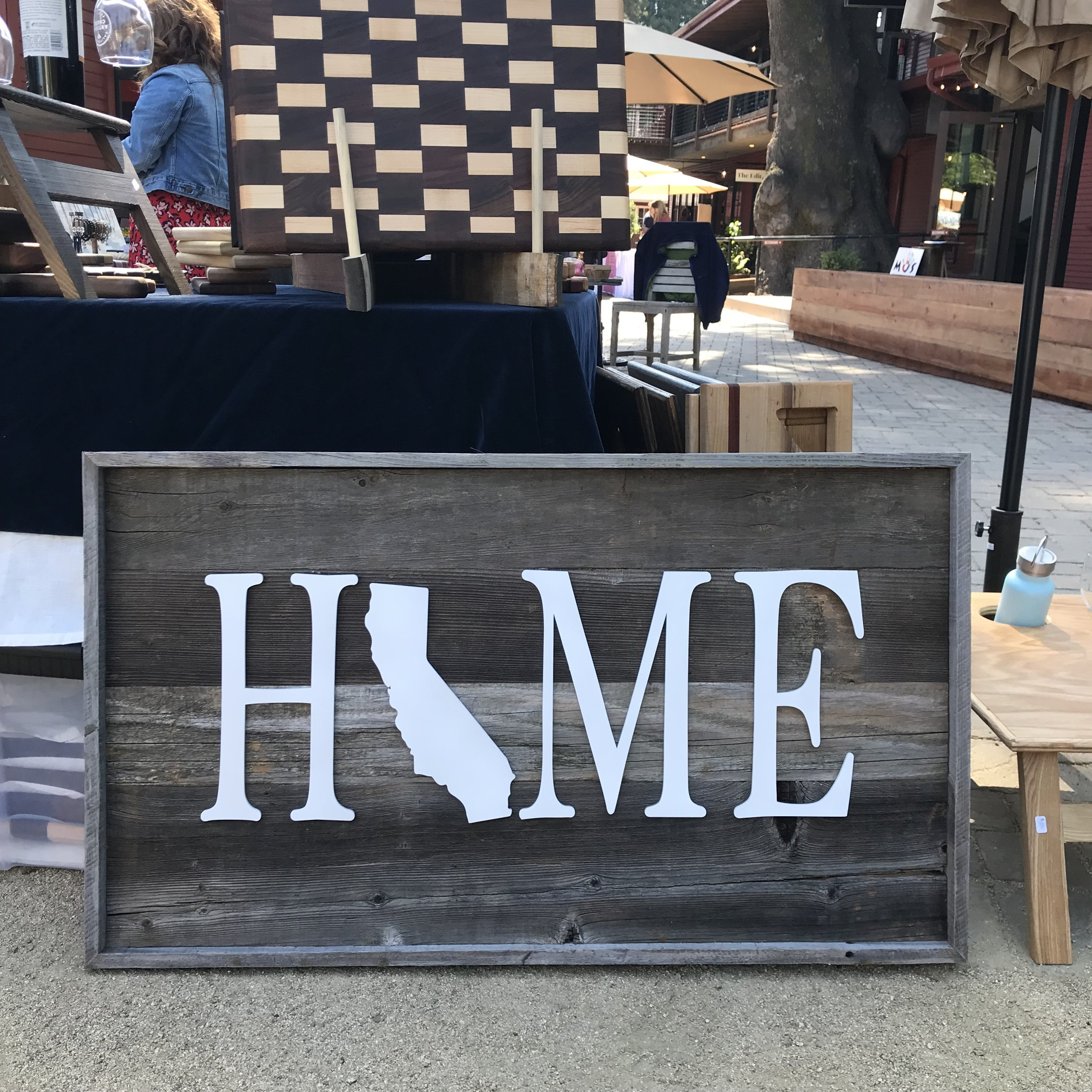 "Our ""California Home"" sign was made using reclaimed redwood fence boards. We used our laser to cut out HOME out of birch plywood. We then painted the letters and glued them onto the reclaimed fence background. We finished it off with a Hangman french cleat on the back to facilitate hanging."