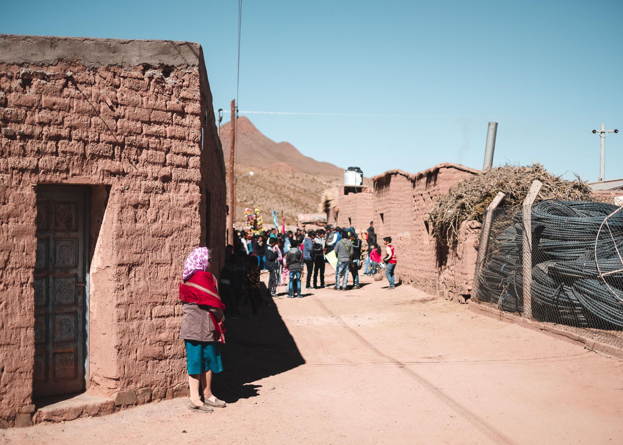 Etwas abseits beobachtet eine Frau den Umzug durch den Ort Huáncar.