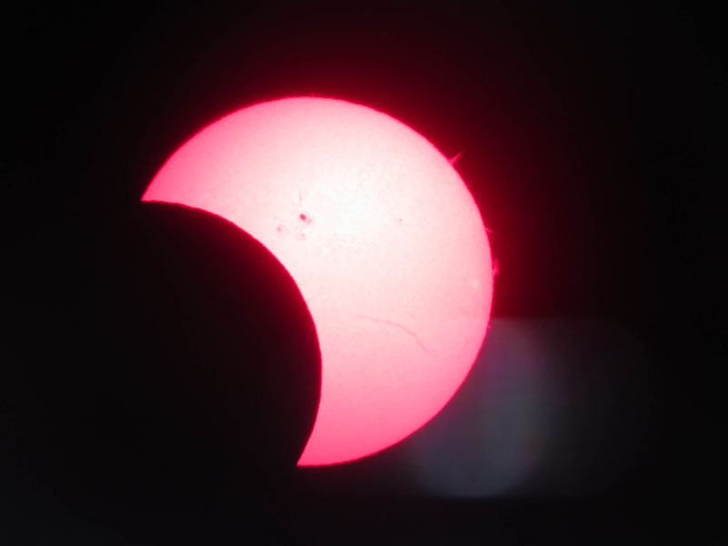 Figure 2-3: An afocal image with a smartphone camera, handheld, of a partial solar eclipse through a Coronado Personal Solar Telescope.