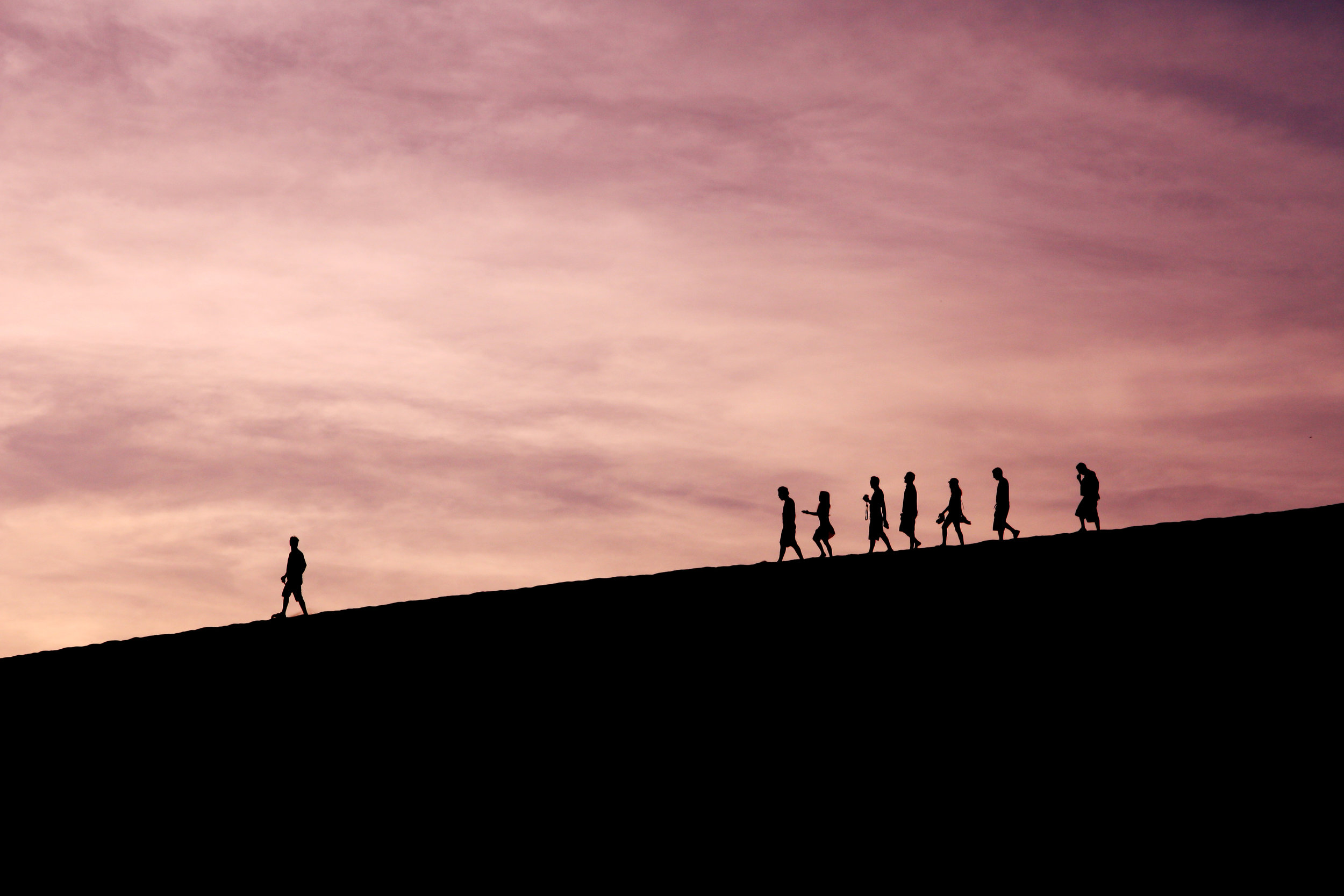 A leader leading his friends down a hill at sunset.
