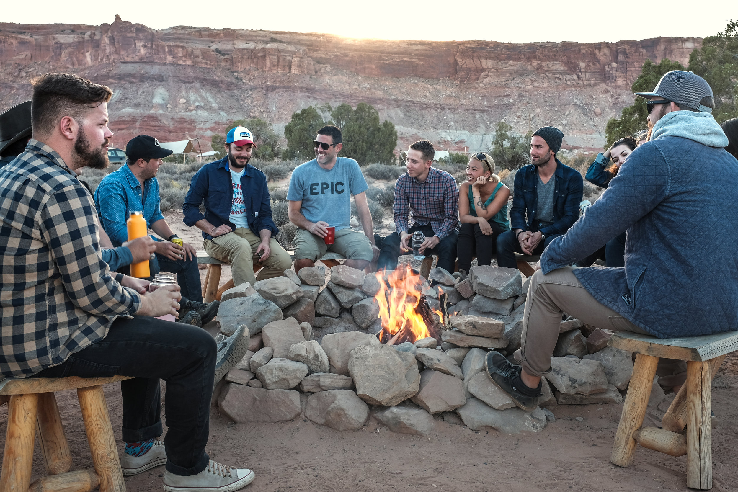 A group of friends sitting around an outdoor fire.