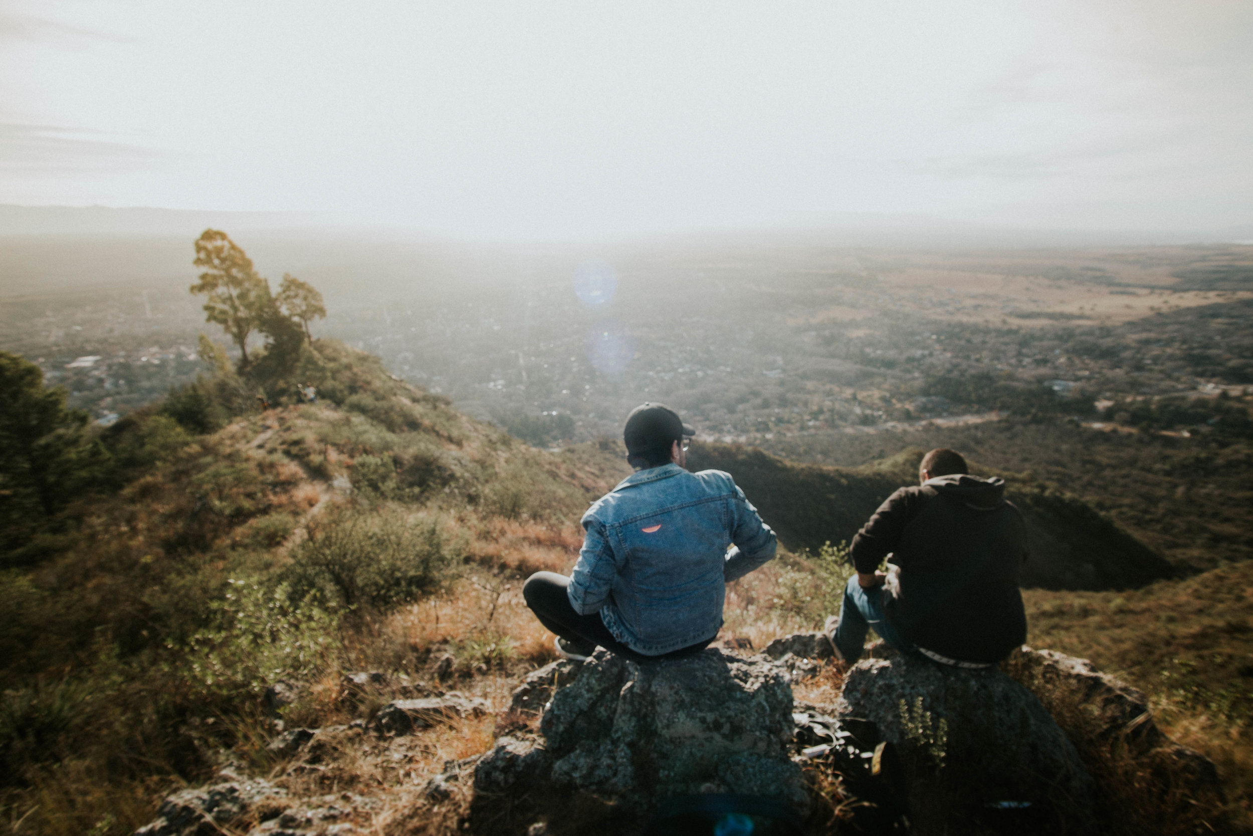 A friend comforting another friend while sitting on a mountain overlooking the desert.