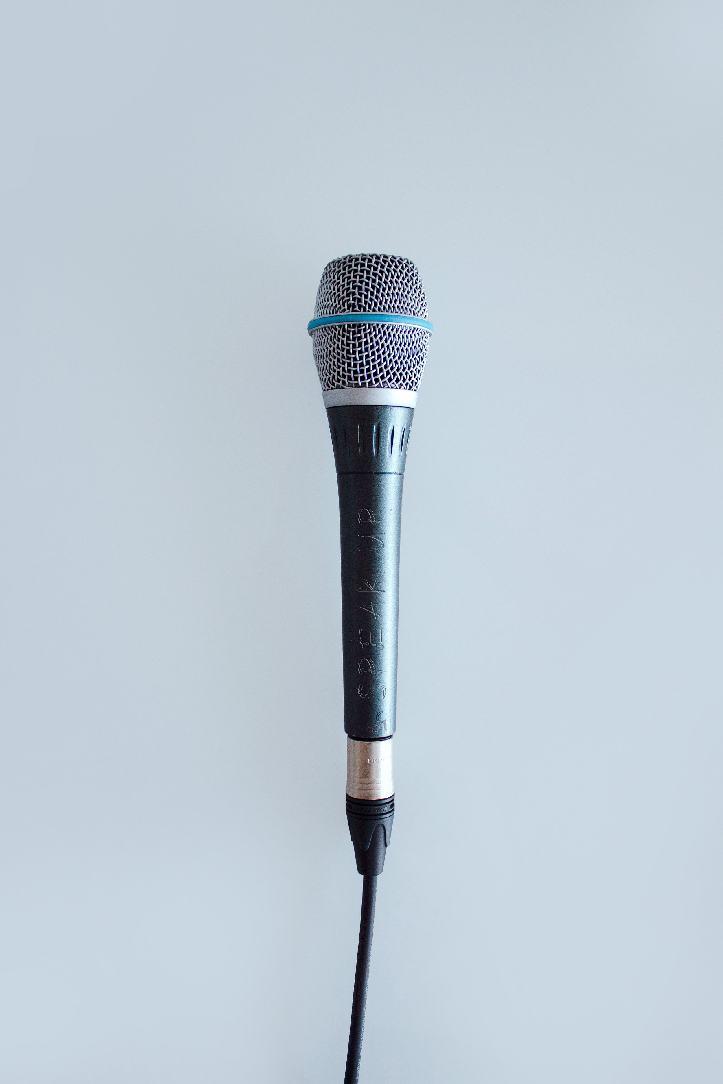 A microphone against a blue background that you can use to speak up against negative thoughts.