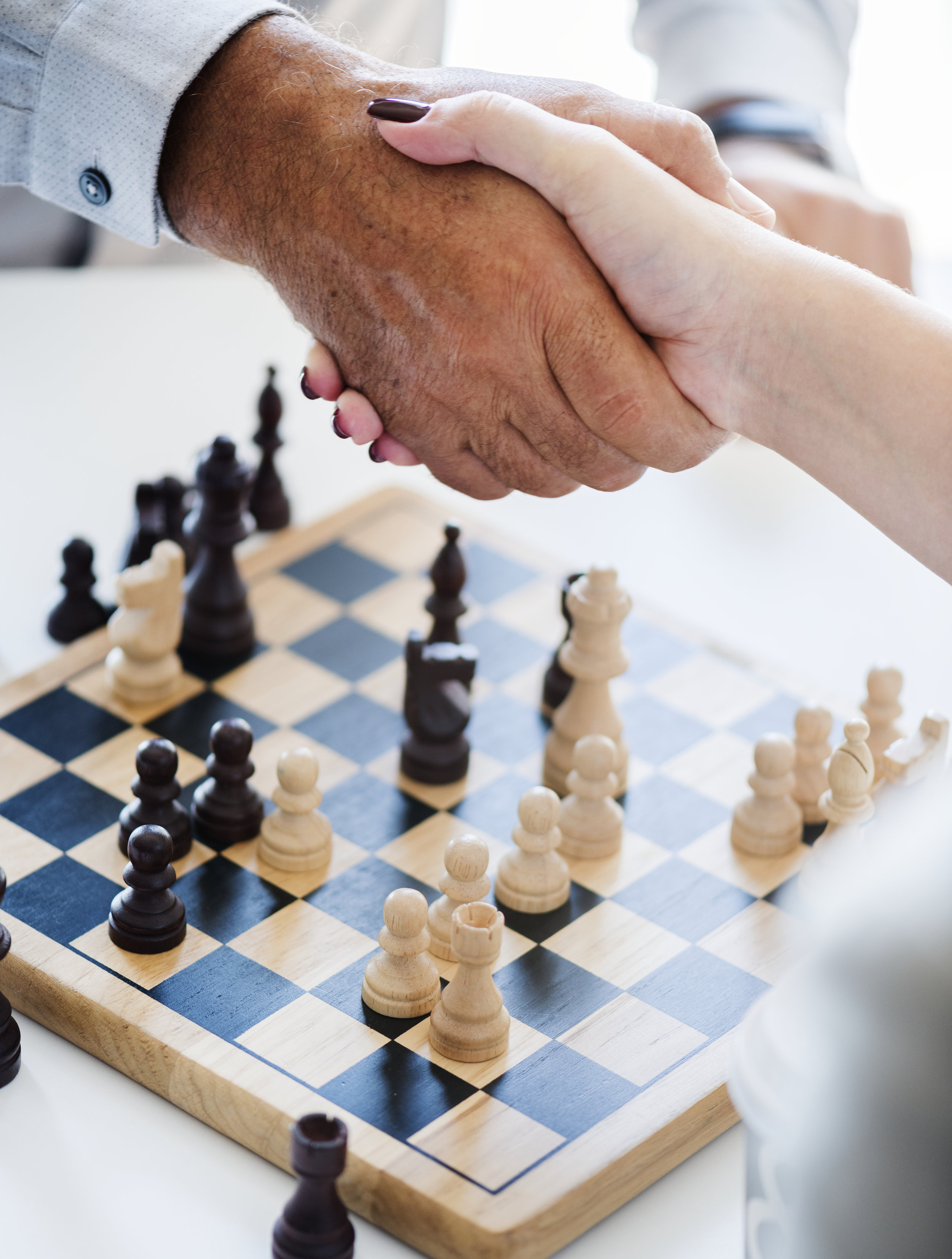 A man and a woman shaking hands over a game of chess.