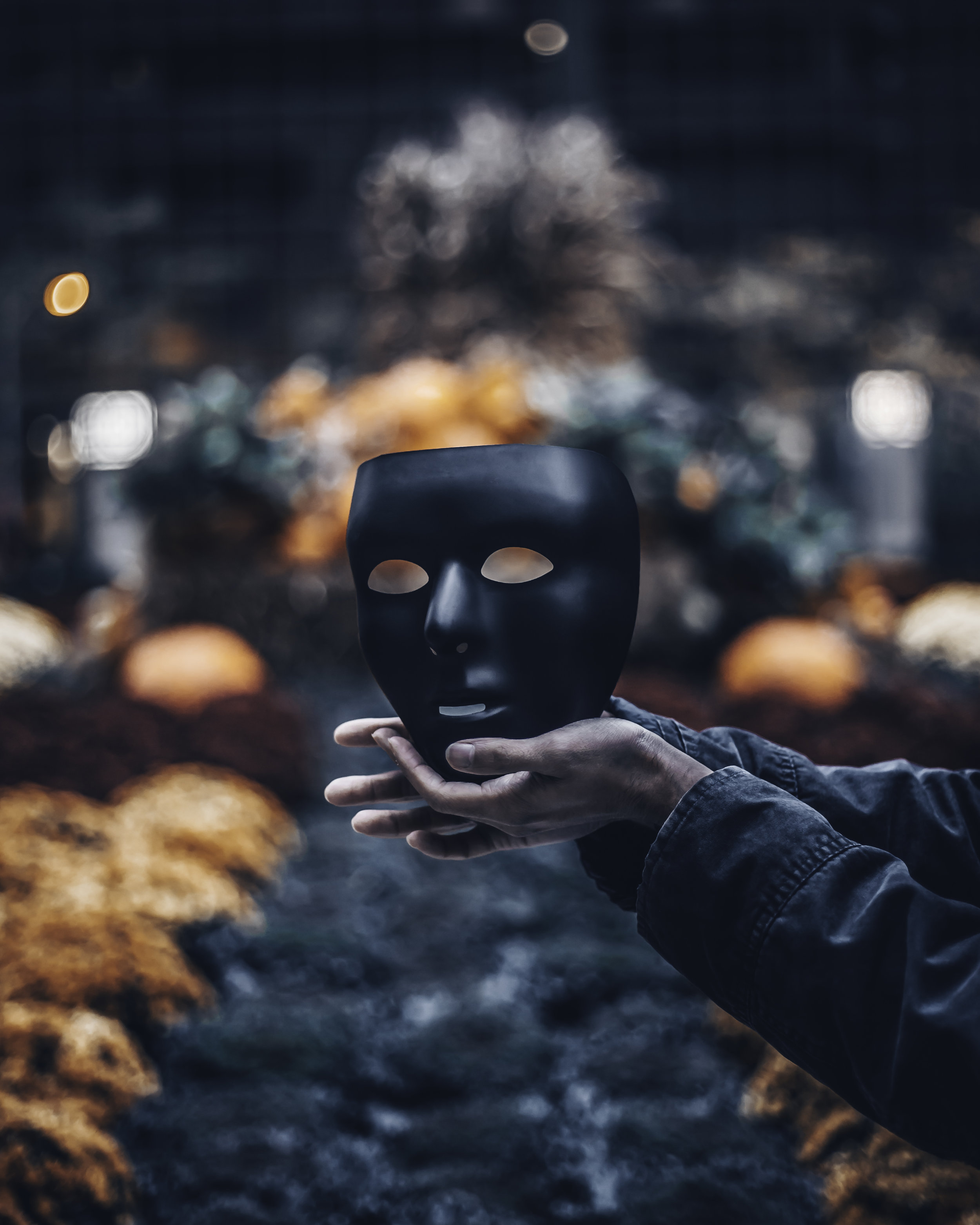 A man holding a mask that represents the 25th law of power.