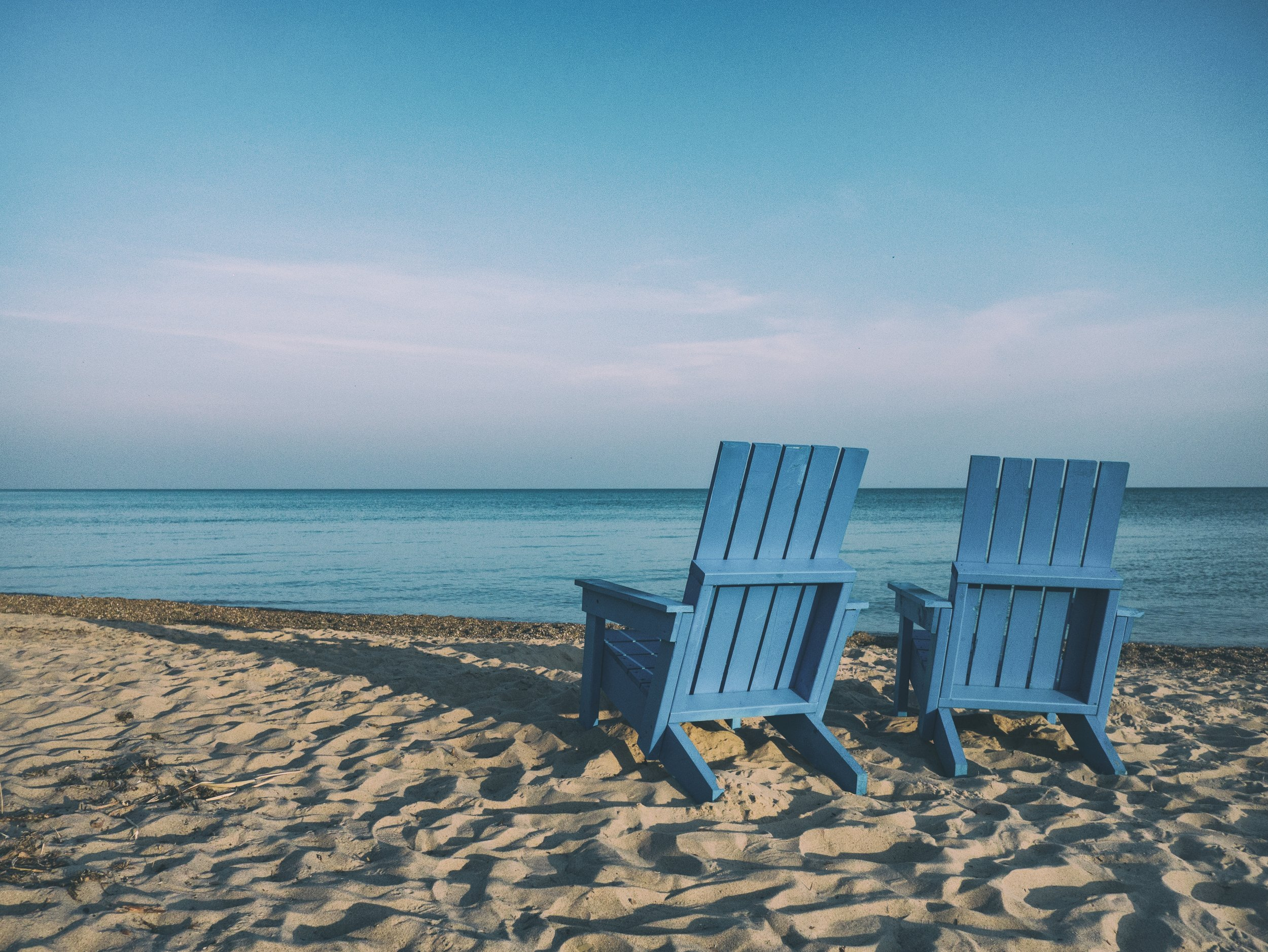 Two blue chairs on the beach.