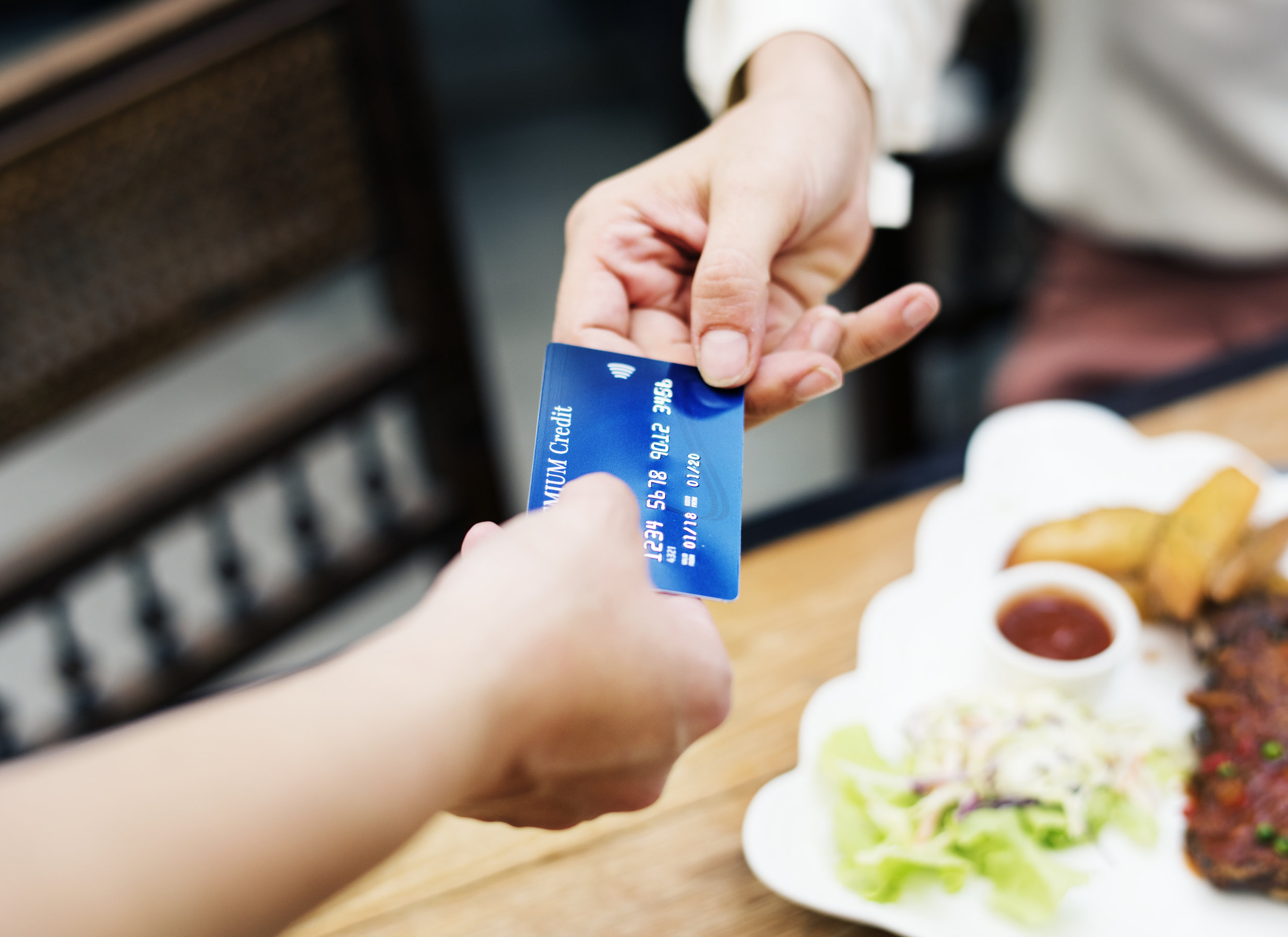 A person paying for a meal with a credit card.