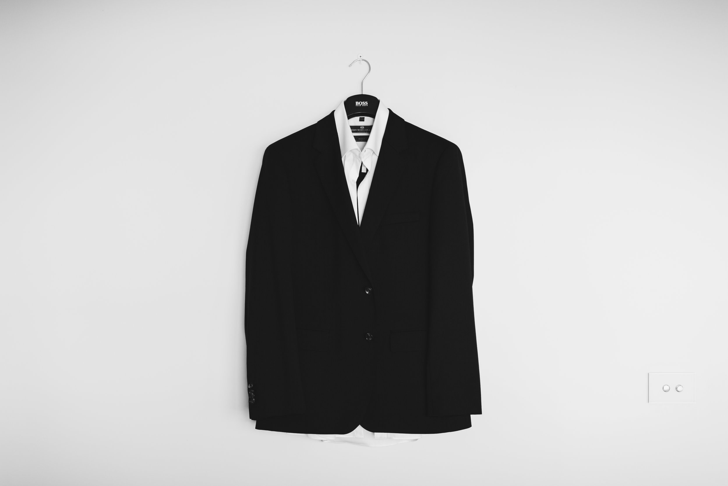 A black suit hanging from a hanger.
