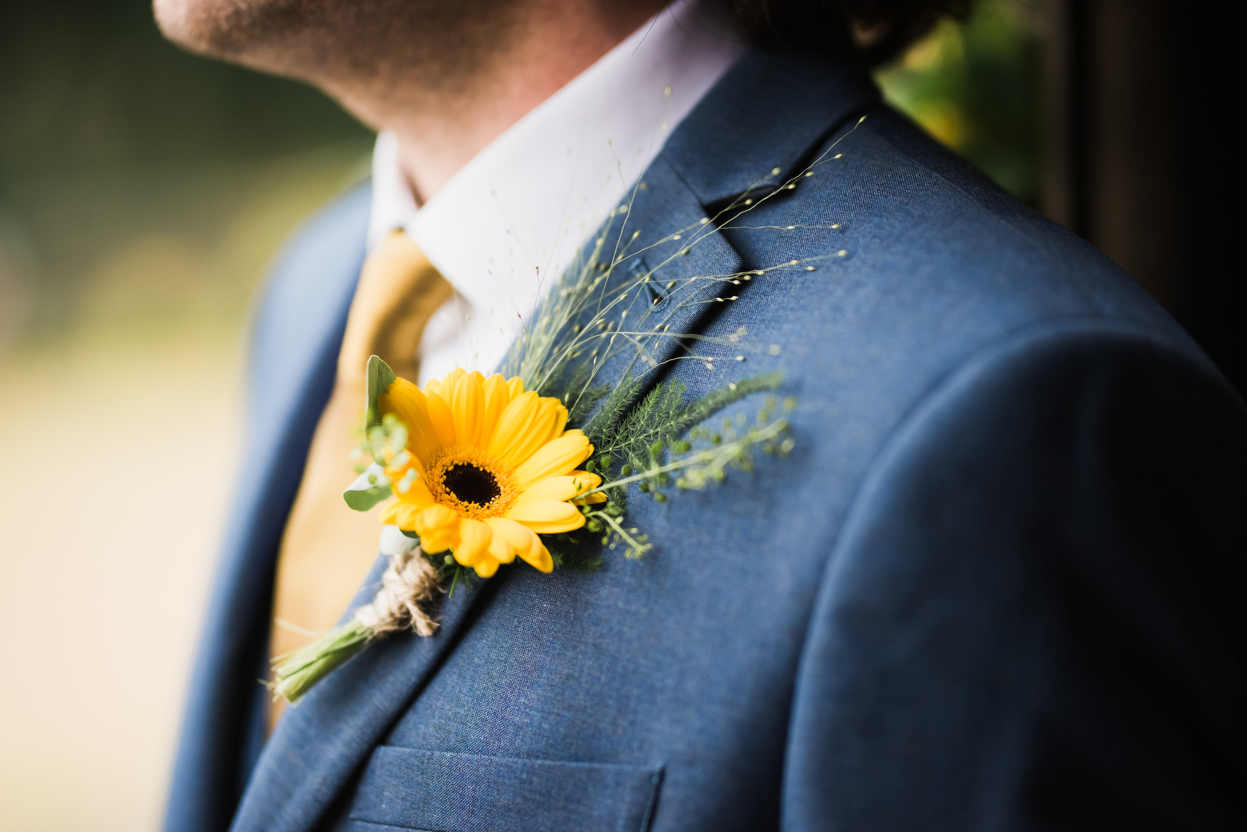 A suit lapel with a yellow flower pinned to it.