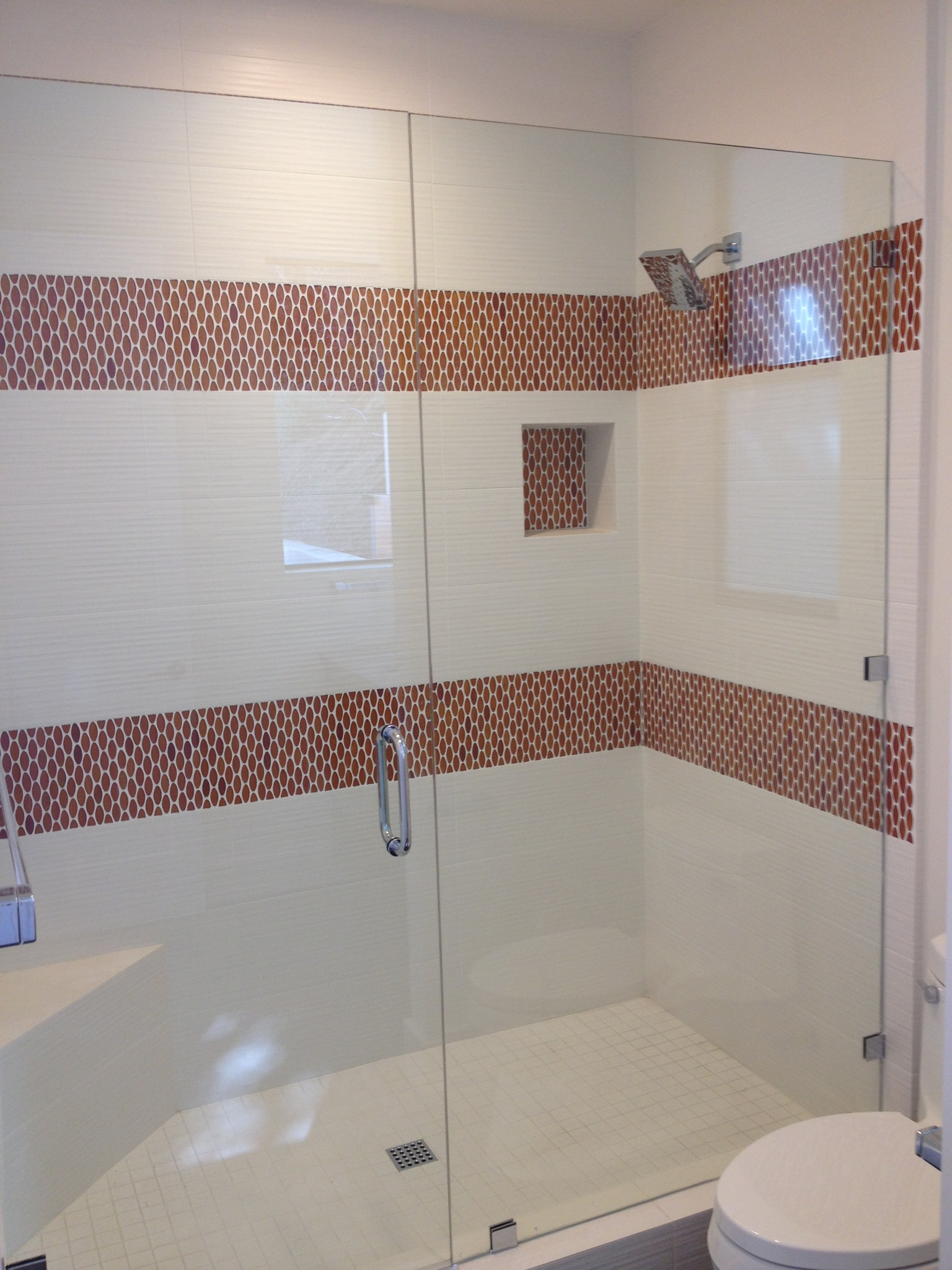 white ceramic tile with orange glass mosaic shower