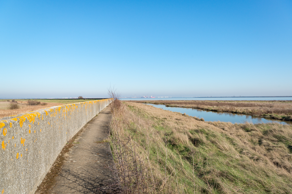 Walking along the sea wall by the Thames estuary at East Tilbury