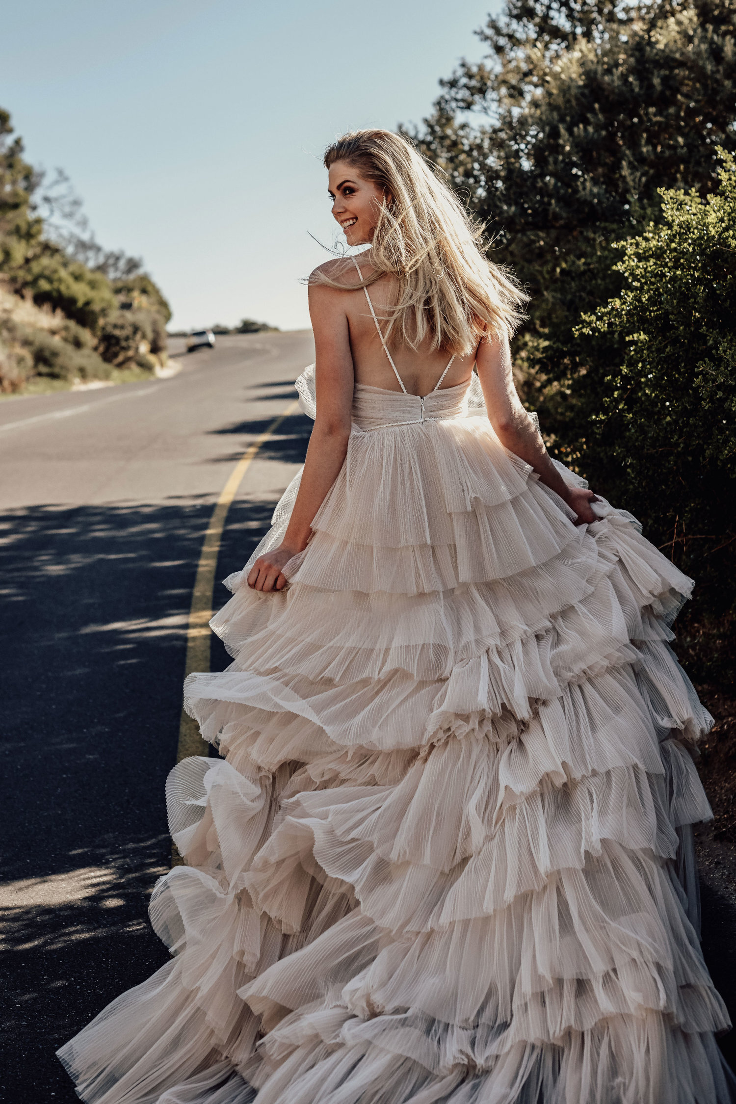 bells - The Bells Gown is an absolute scene-stealer. Layers upon layers of pleated tulle cascade from hints of blush into ivory. The deep plunged neckline adds sensuality and lightness, and the straps and subtle belt are hand-beaded for a touch of sparkle.