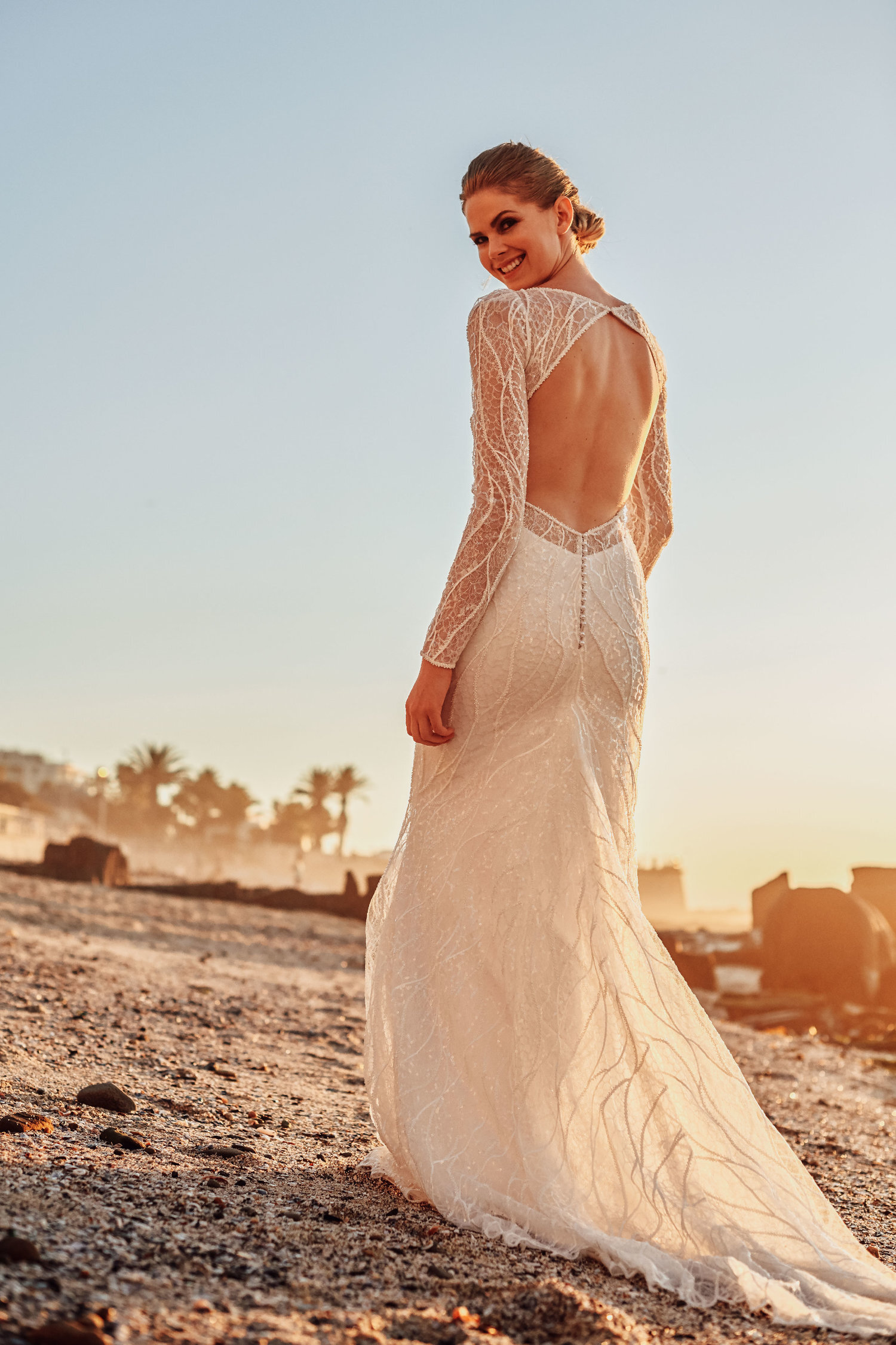 Nymphea - The Nymphea Gown lends a subtle sparkle to the bride that wants to catch the eye. Waves of beads and sequins wash over sea foam white, creating a classic but striking silhouette. A slight train spills from the figure-hugging form, and an open back lends some sensuality.