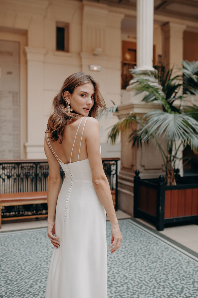 CANNA - The Canna gown is an effortlessly sexy slip dress with a dramatic slit at the centre front. This simply modern dress also features a trendy bustier cut top, and is made head-to-toe in luxurious Italian satin. Perfect for the minimalistic bride.Colour - Ivory / Sizes - 6-16