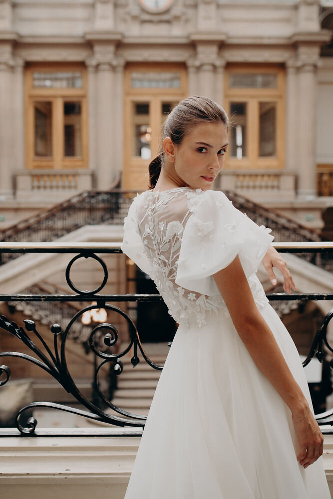 BEGONIA - The Begonia gown is all statement with puff sleeves, dappled with voluminous blooms that spill onto the bodice. These details accentuate an otherwise cleanly minimalist look, ideal for the bride with flair. This gown features a high-low hem, or a standard floor-length hem.Colour - Ivory / Sizes - 6-18
