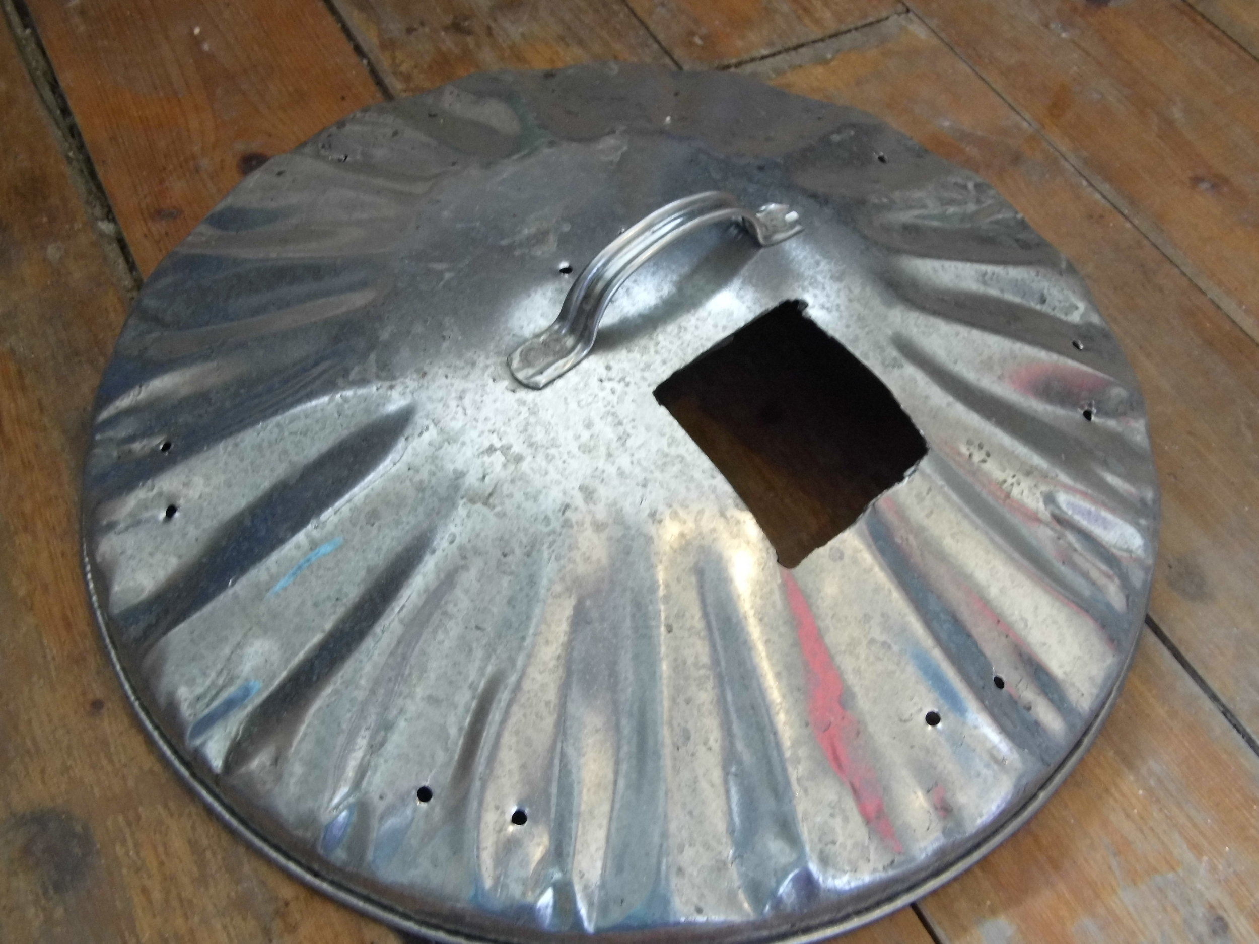 1. A hole is cut in the lid at least 10cm/4inches in diameter. Pairs of holes are drilled at intervals around the edge of the lid and also near the centre.