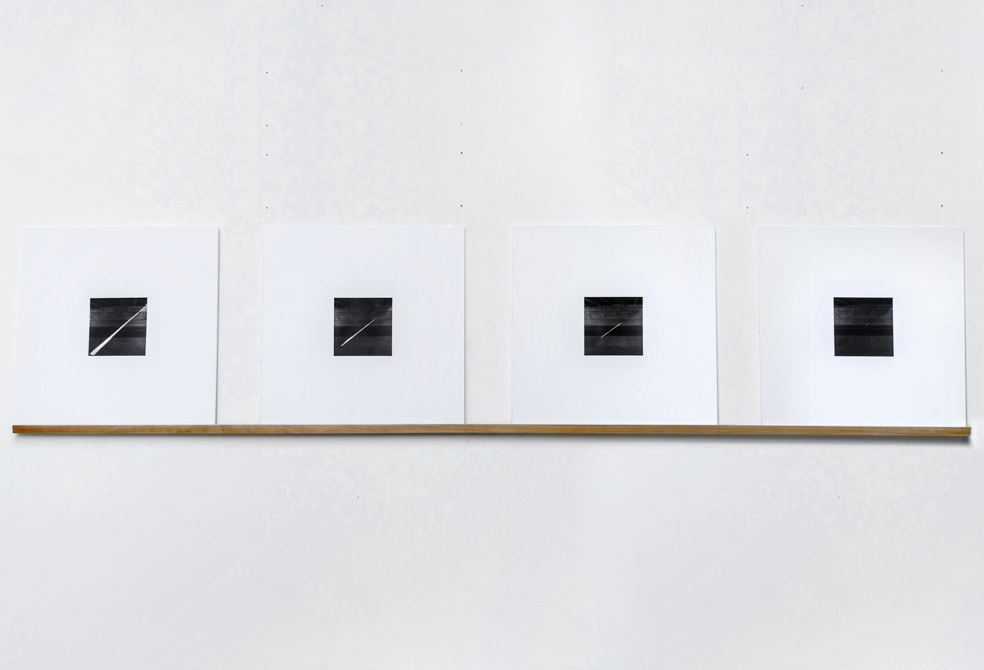 "Half of an Hour , 20"" x 20"" each, series of 4 silver gelatin photographs taken from one viewpoint (documenting a sliver of light) with an interval of 10 minutes between each photograph. Silver gelatin photographs, mat board, wood shelf. 2013"