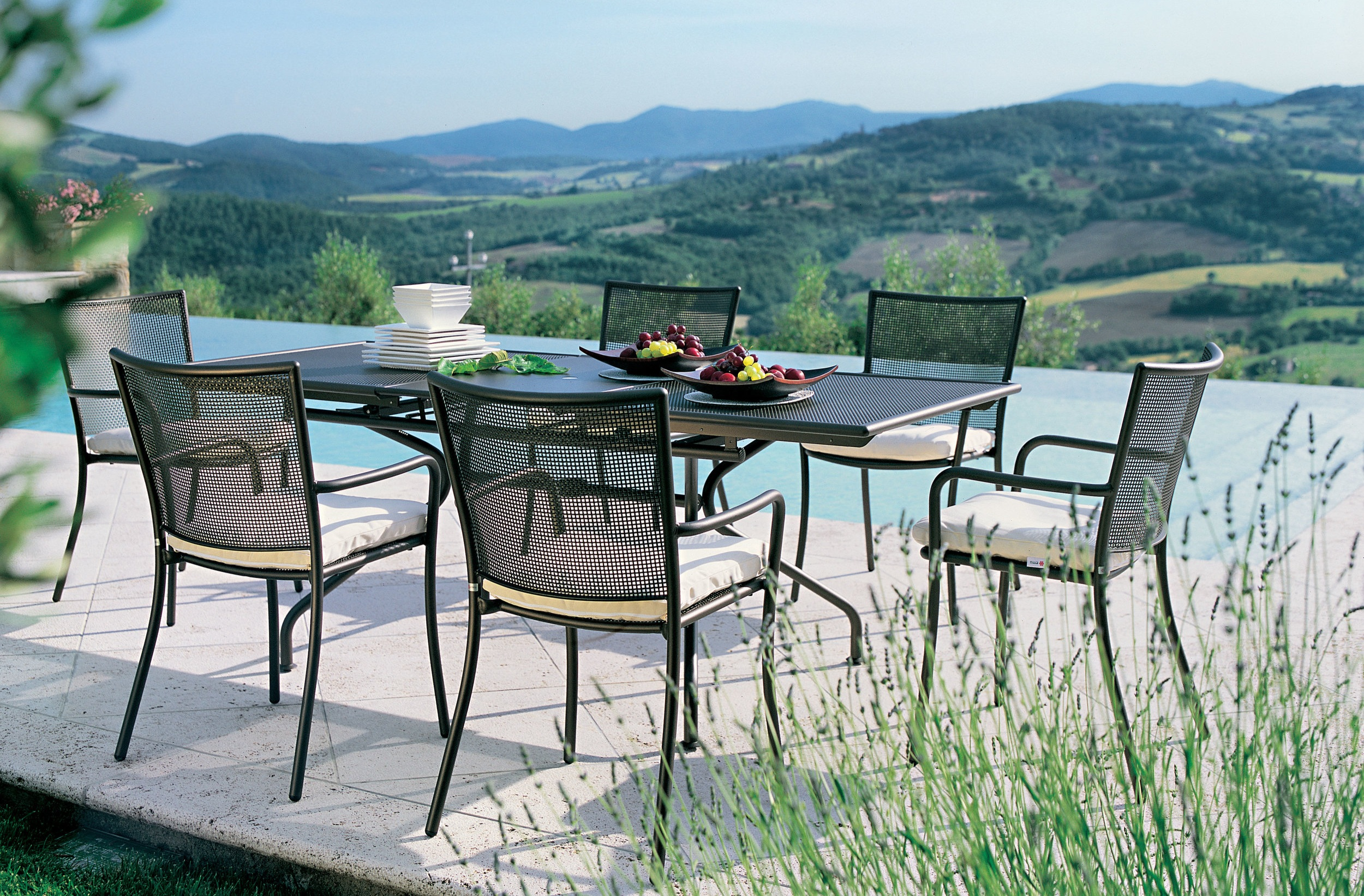 Athena Rectangular Table - The Athena table creates a perfect union with the sessions of the same series. The plan repeats the ornamental motif of the interwoven sheet metal typical of the armchairs of the family and is designed to provide a perfect service functionality and practically for hours of outdoor relaxation.