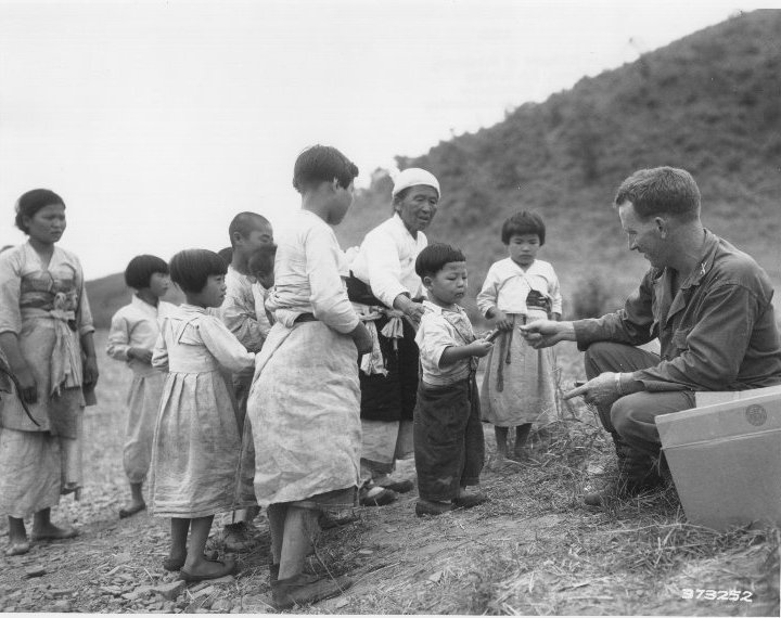 Korean War SC Coll Box 1, RG6s-KWP.27    1st LT William Millward of Baltimore, Md, Civil Assistant Officer, 5th Cavalry Regiment, 1st Cavalry Division, distributes candy to Korean children at a refugee collecting point in Western Korea.