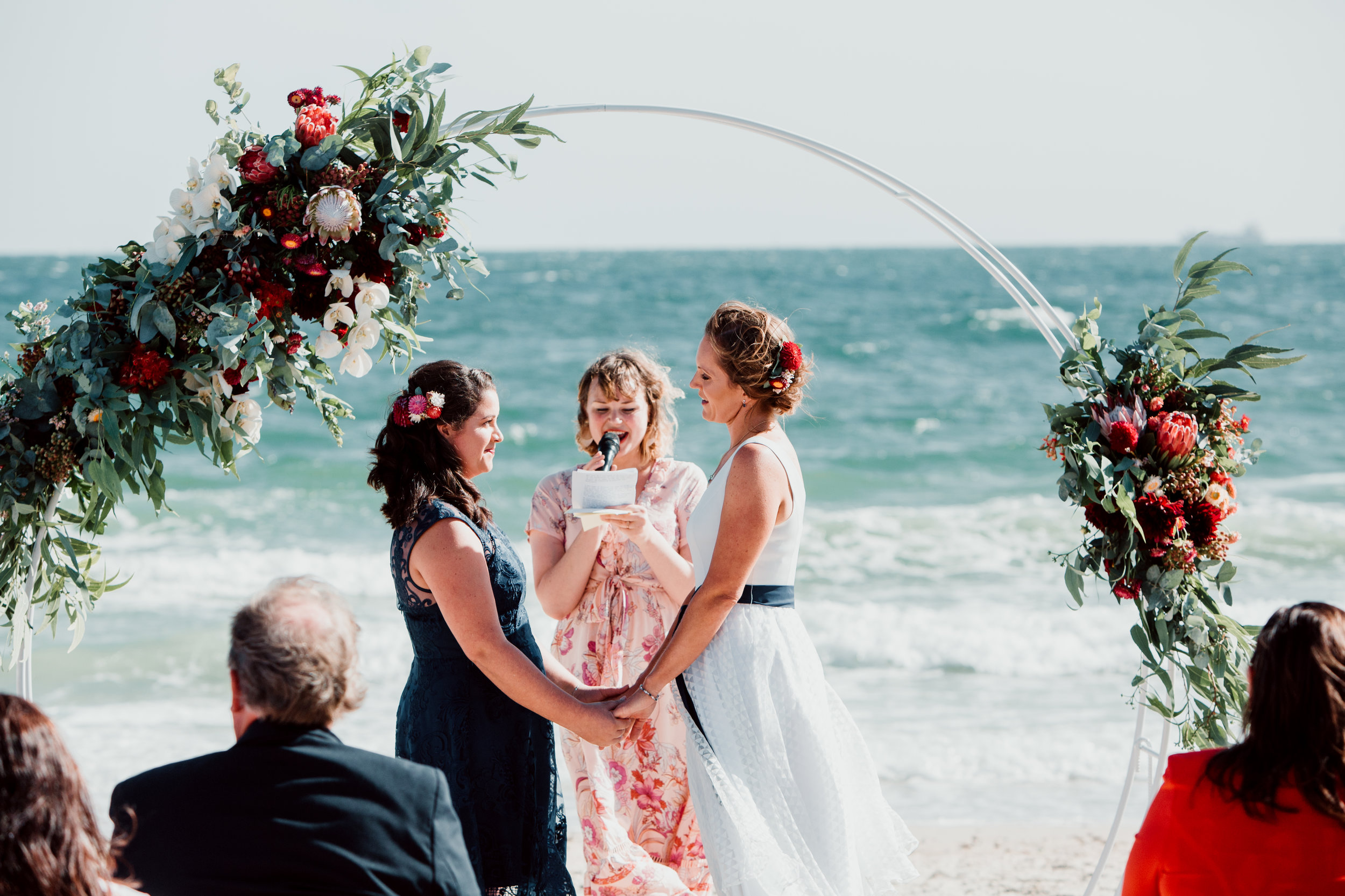 Rebecca & Kara   Venue: The Sandbar  Rebecca & Kara wanted a simple wedding with native flowers set against the sunset on the beach.  Both brides opted for floral hair pieces instead of bouquets, and got married in front of a floral arbour.  Photographer: Neil Hole Photography