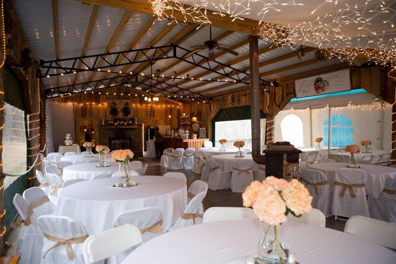 "Pavilion - The Cabin at the Lodge wedding venue offers a variety of amenities for hosting your special event. ""The Pavilion at the Lodge"" offers a 24' X 66' rehearsal, reception venue, complete with weather panels that can be lowered in the event of inclement weather. This unique rustic venue features a full size kitchen, a stone fireplace, a wood burning heater, a 55"" flat-screen television, a DJ / band stage area, and a bar. The pavilion can seat approximately 100 guests at 5' round tables or 175-200 guest in chairs only."
