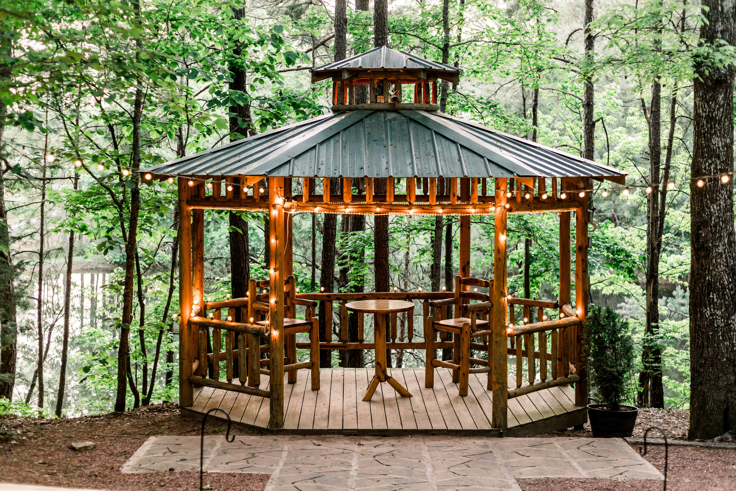 "Gazebo - The grounds at the Cabin at the Lodge provide numerous locations for your ""I do's"".The 12'x14' rustic handcrafted cedar log gazebo sits nestled in tress overlooking a 1½ acre lake. The gazebo seats approximately 175-200 guests with cedar log benches."